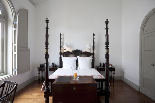 Four poster bed in dark mahogany with white Belgium linens and antique chest  Design Thought:  Measure ceiling before committing to a four poster or canopy bed.  Guidelines suggest a minimum of 12 inches clearance from the height of the ceiling to the top of the post.