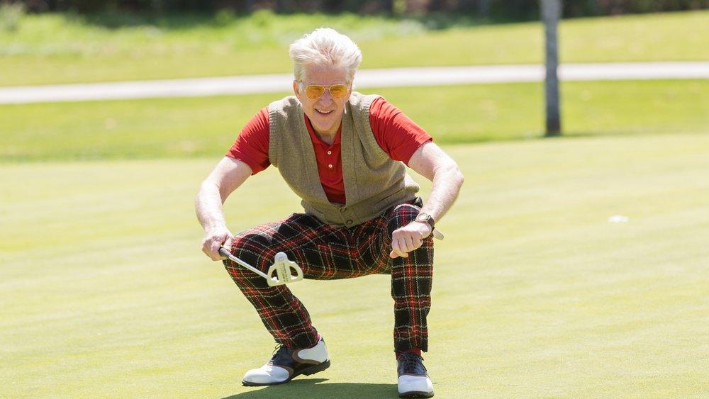 Congressman Cliff Williams (Matthew Modine) eyes a putt before Virginia finds him on the golf course.