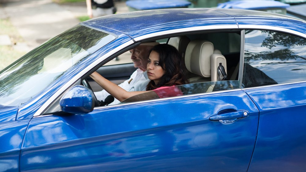 Vanessa (Anna Cecelia) and Abuelo (Ruben Rabasa) drive off in search of a rare car part.