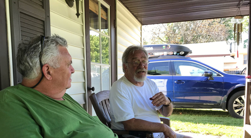 Old guys sitting on the porch, chatting with each other and the bunnies