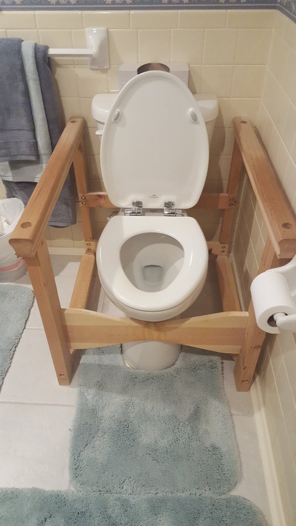 Before - The toilet was too low for my client to comfortably sit down and stand up. The wooden armrests were made by a family member.