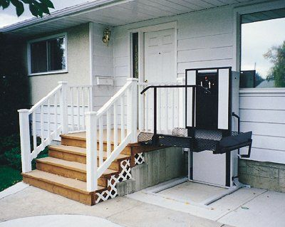 Vertical platform lift next to small porch with four steps to enter door. Photo by Mobility Express