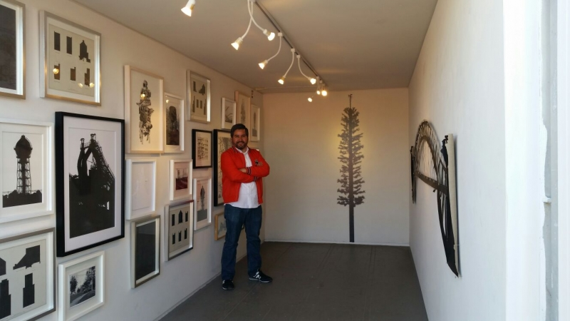 Daniel with installed exhibition, 12-15