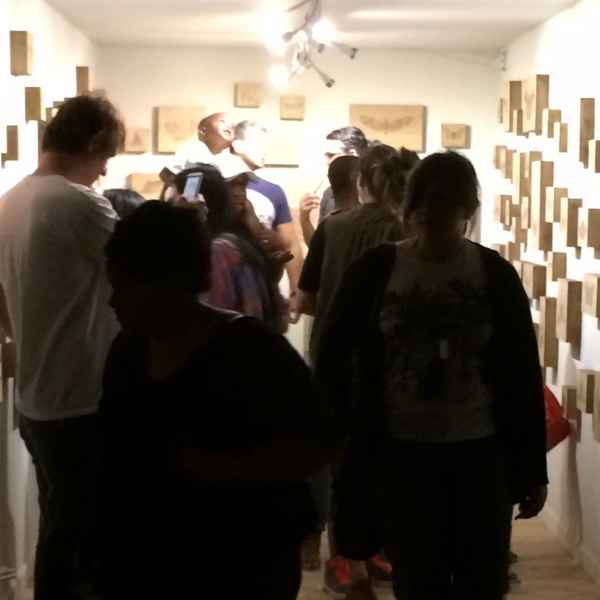 People enjoying Lexie's installation of her wood-burned moth drawings, First Friday, 5-1-15. Photo credit-William LeGoullon