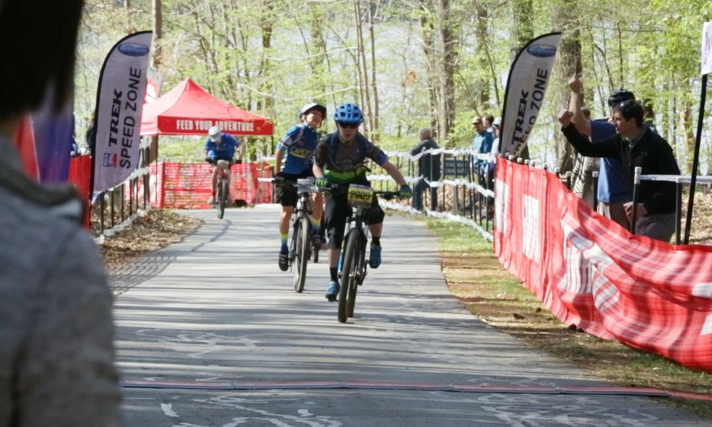 Middle school rider, Marshall Anderson races to the finish line with Coach Hensley cheering him on.