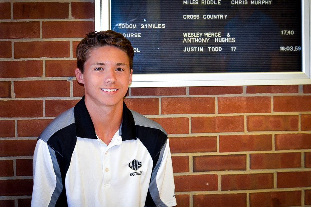 Todd at the Ledford High athletics board that shows the new cross country school record time.    Photo by Eliot Duke.