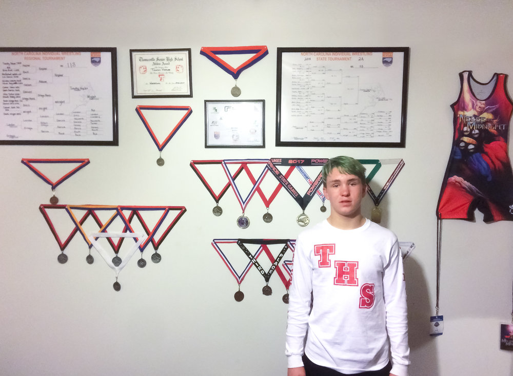 Hepler poses with his wall of impressive achievements.  Photo by Brad McNease.
