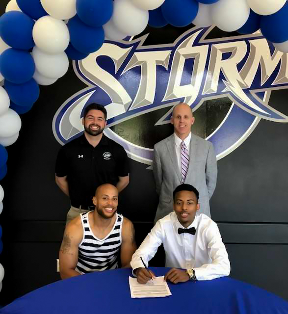 Asst. Coach Dylan Hall (back left), Coach Matt Ridge  (back right) , Jahlen King  (right)  and his family.