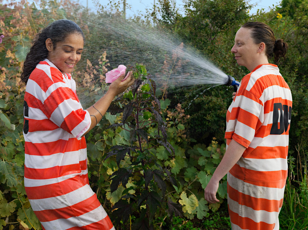 Lucas Foglia -  Vanessa and Lauren watering , GreenHouse Program, Rikers Island jail complex, New York, 2014. © the artist and courtesy Fredericks & Freiser Gallery, New York.