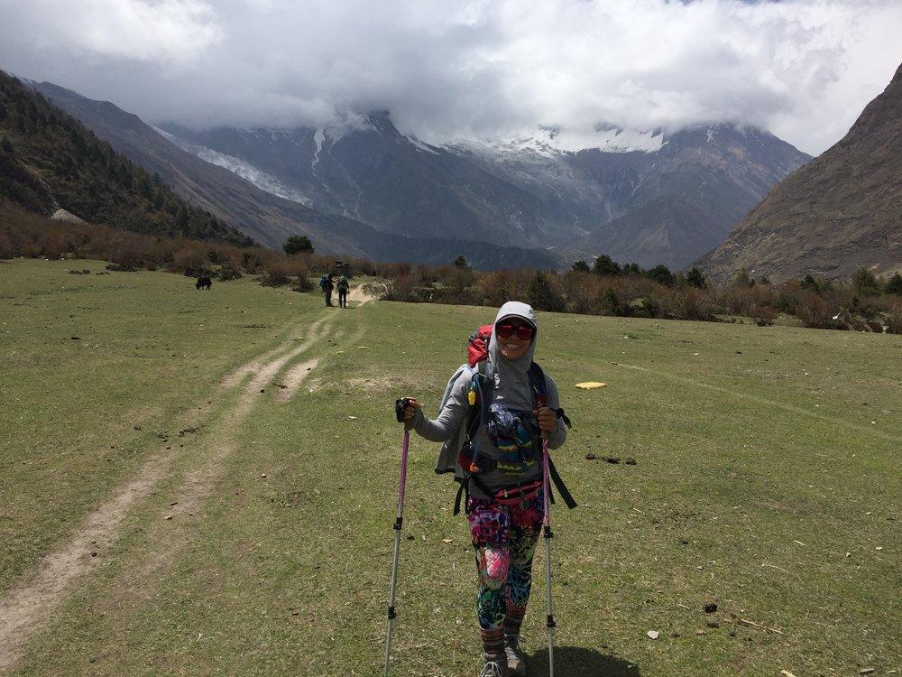 Thung lũng cỏ xanh mướt rộng mở và núi tuyết sơn hùng vĩ phía xa