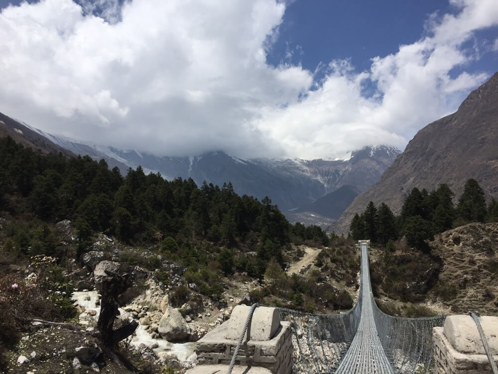 Crossing suspension bridge in Manaslu Conservation Area