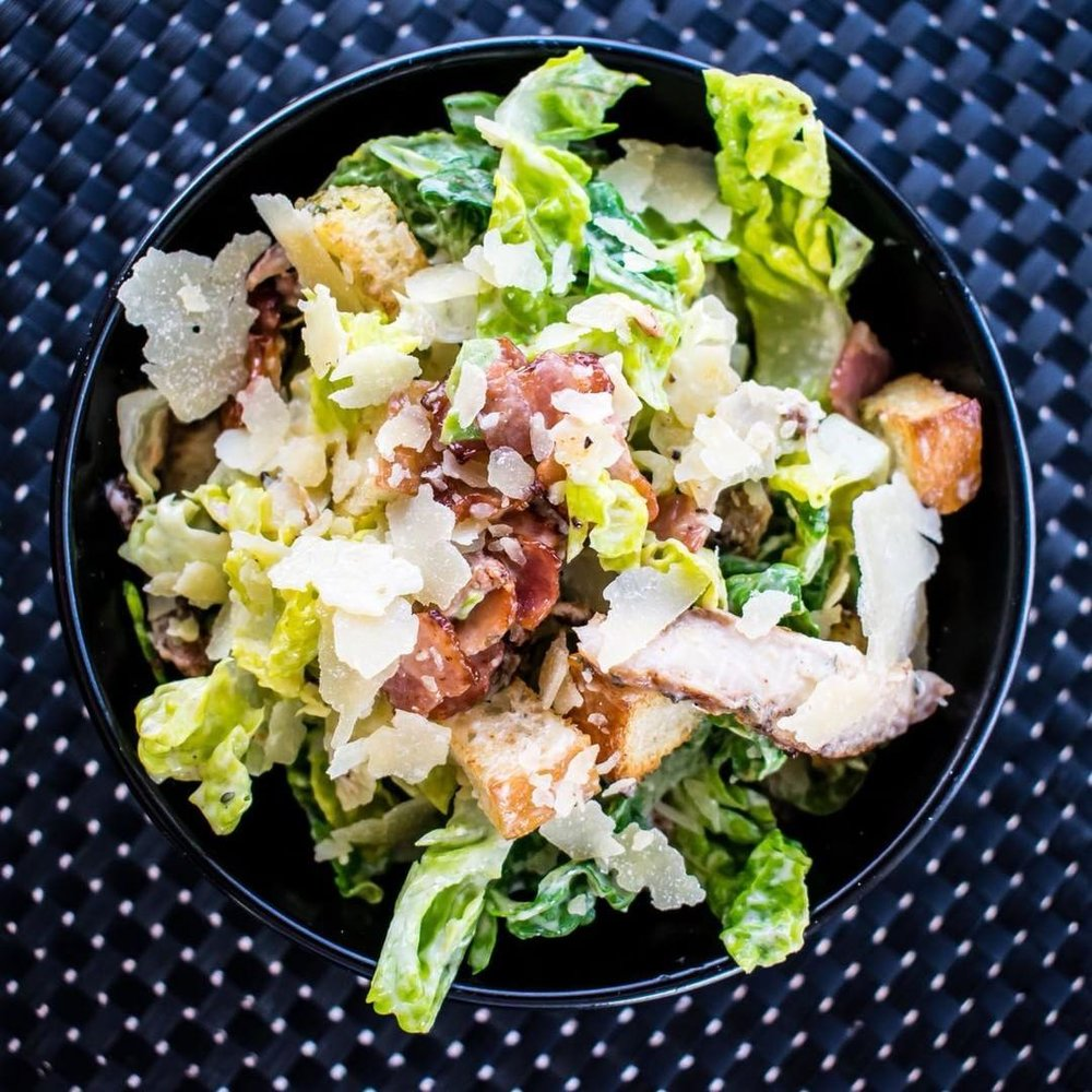 Caesar Salad  - Warning - Highly Addictive! This salad is a mix of anchovies, bacon, croutons chicken and lettuce, all covered with our house-made caesar dressing, and lightly garnished with parmesan.