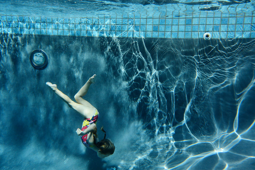 young girl swims underwater in New Jersey swimming pool