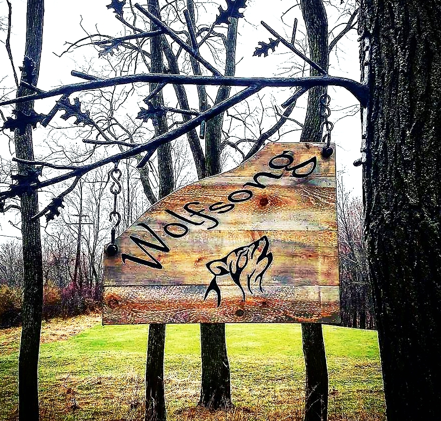 This beautiful sign was custom designed and hand-carved by Craig. Iron bracket (Iron Garden Structures By: Joe Miller)