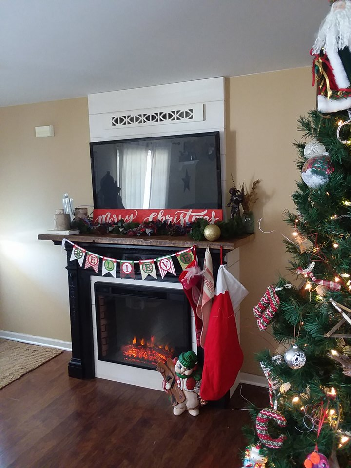 Craig built this electric fireplace into a vintage mantle where there was once an empty wall. He made shiplap and used that and barn wood floor boards to create a faux chimney and mantel.
