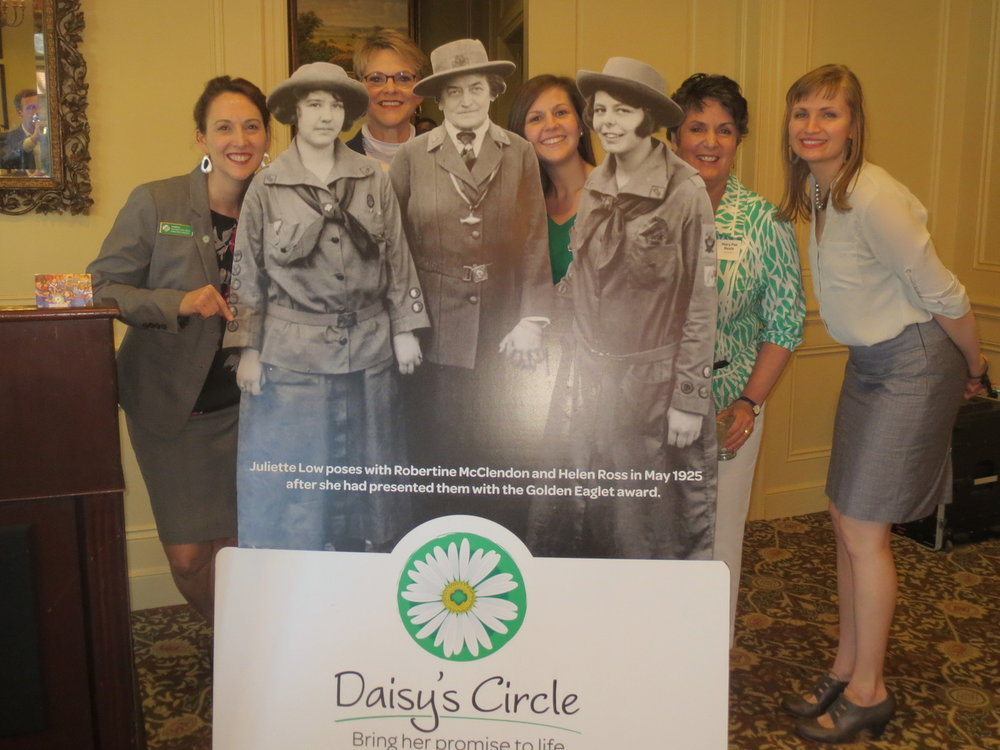 Girl Scouts of NE Kansas and NW Missouri team posing with a signature  Daisy's Circle  sign at an early launch event for their  Daisy's Circle  monthly giving program.