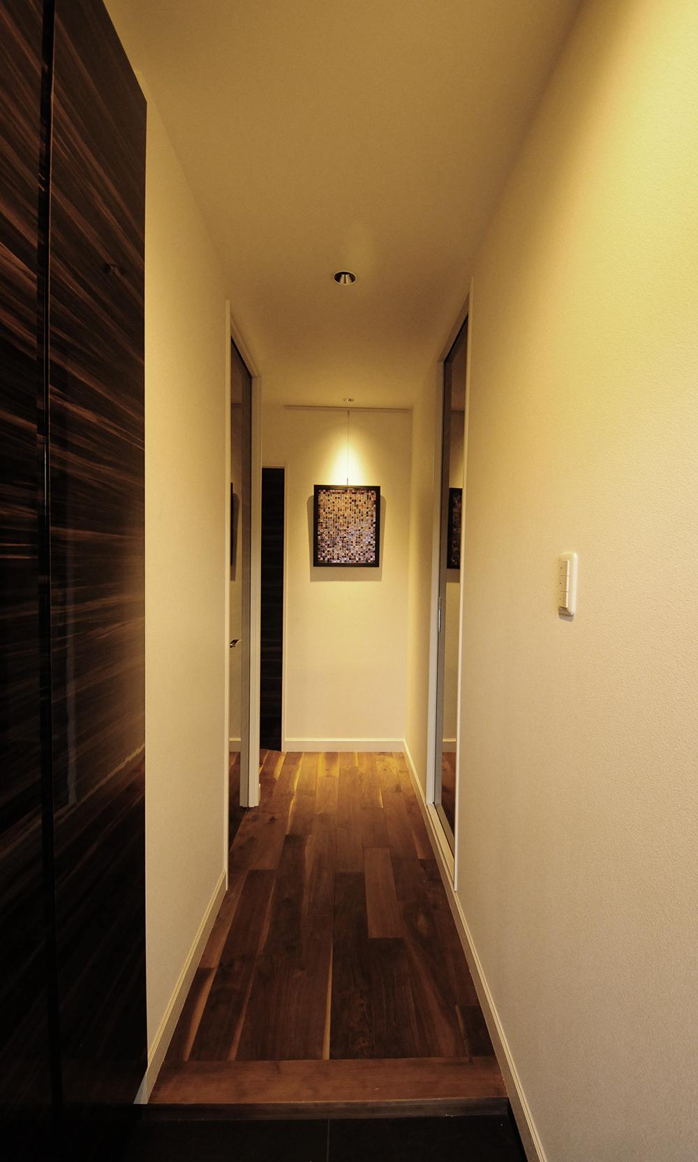 エントランス。玄関を入るとイタリアガラスモザイクアートがお出迎え。ブラックウォールナットの無垢の床が引き立たせている。
