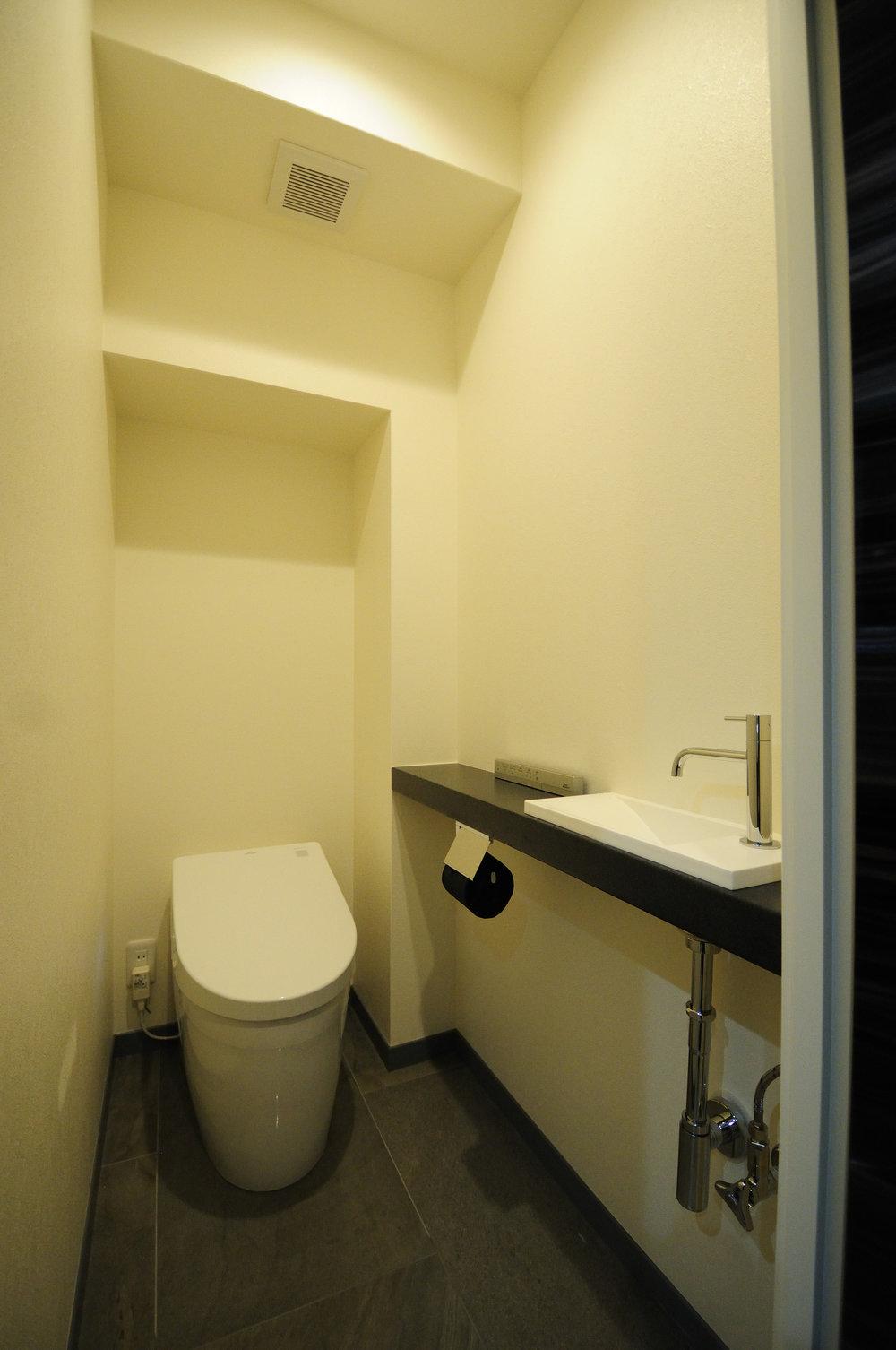 床は洗面と合わせイタリア製タイルで空間を統一。空間に溶け込むようなタンクレストイレと手洗器(CEL430)を設置、洗練された印象に。
