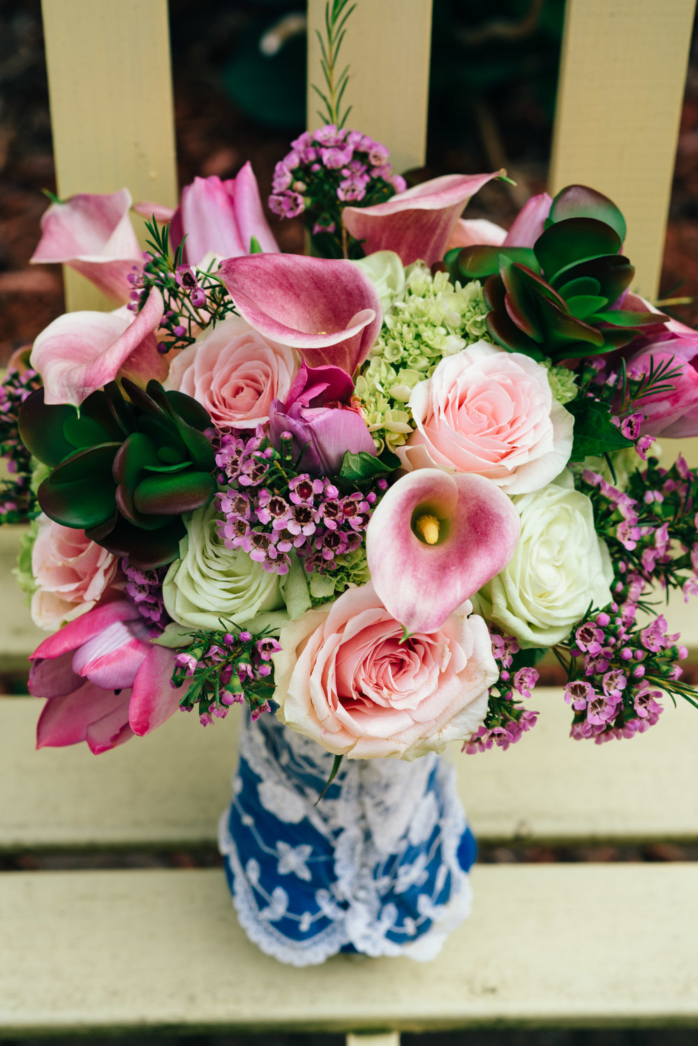 Wedding bouquet by Wedding Elegance by Joelle featuring pink roses, succulents, purple cala lilly's, and purple tulips.