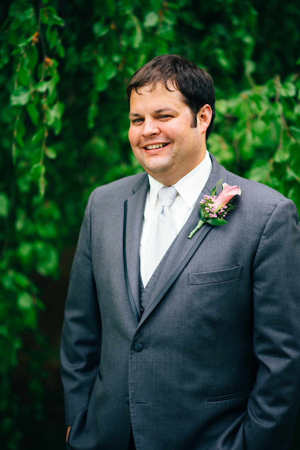 Headshot of smiling groom wearing Vera Wag Black collection suit and cala lilly boutineer