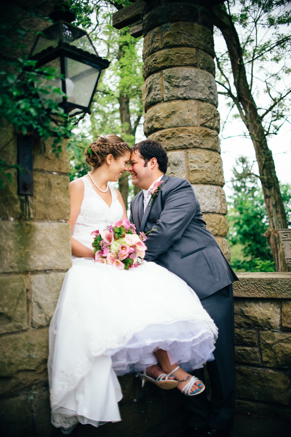 Bride sitting on a stone wall in a garden with groom standing beside her, smiling at eachother