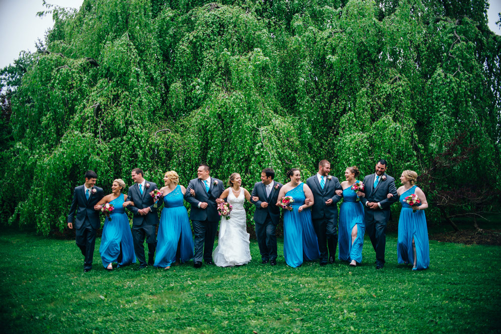 Blue and grey bridal party walking in a garden laughing arm in arm