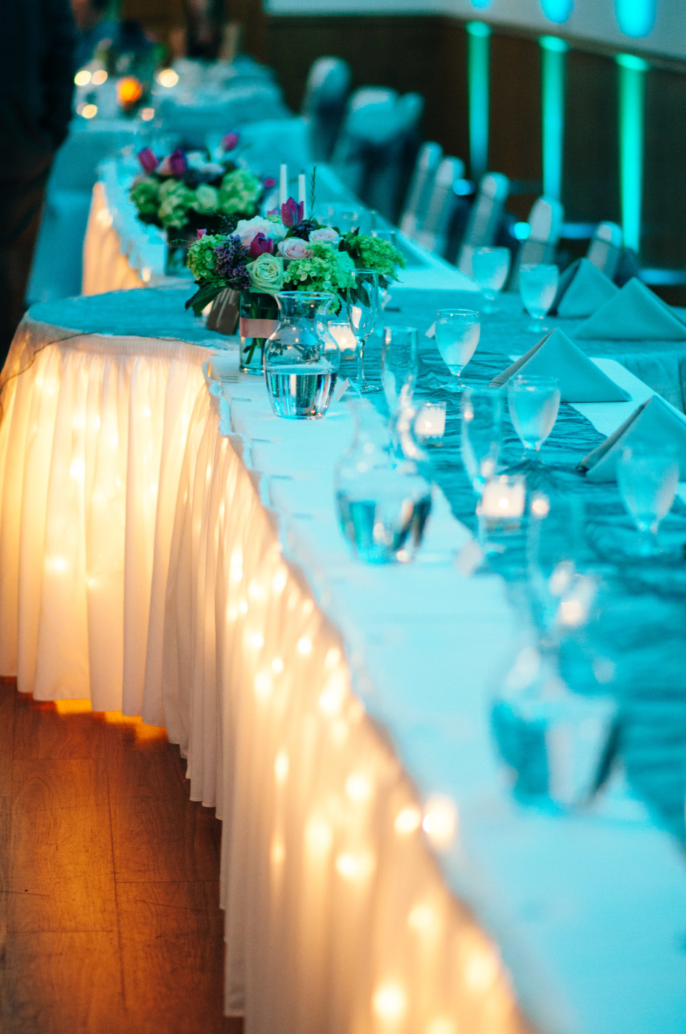 Wedding reception table with fairy lights under a white table cloth and blue uplighting by Dj Jack Labarko