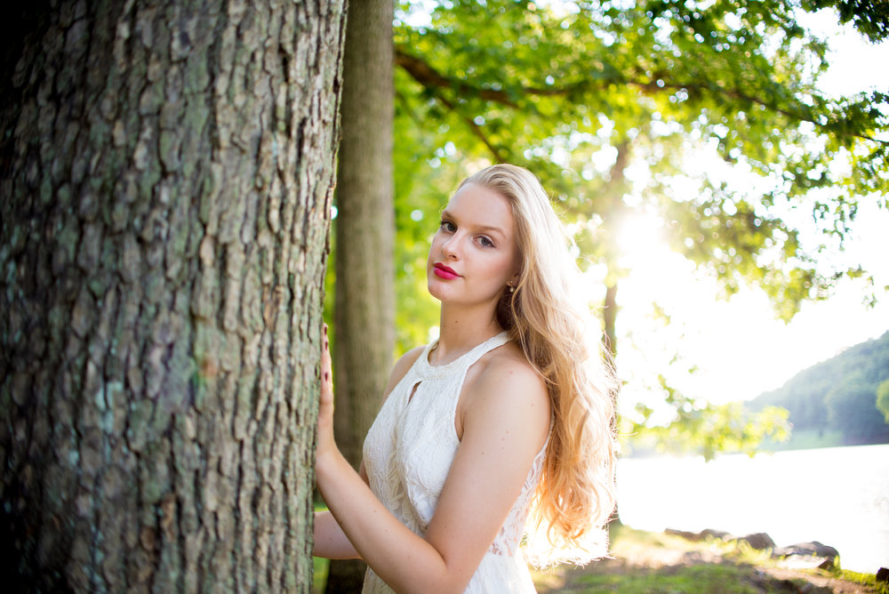 Blonde high school senior model with white lace dress standing by a tree and sunset.