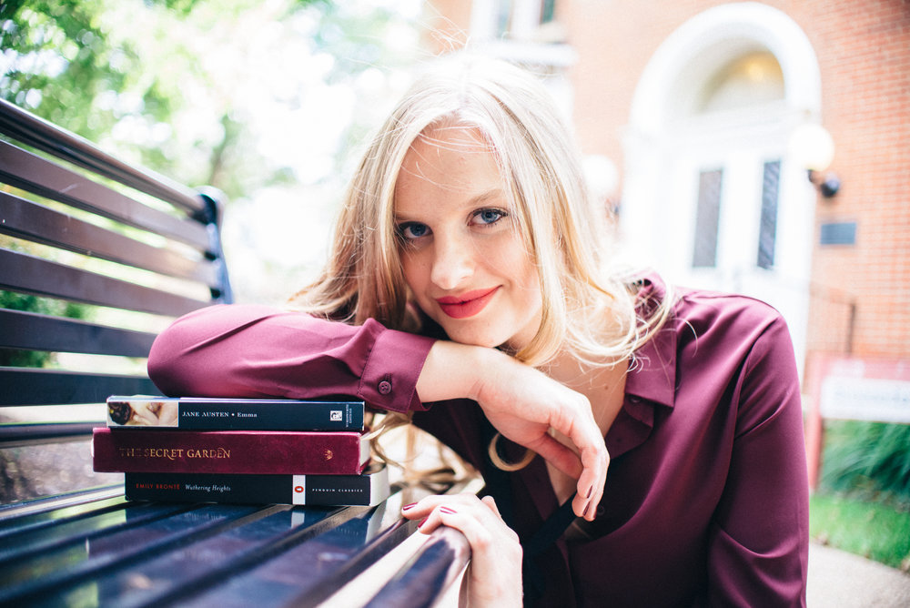 Blonde senior model wearing maroon blouse leaning on a stack of books