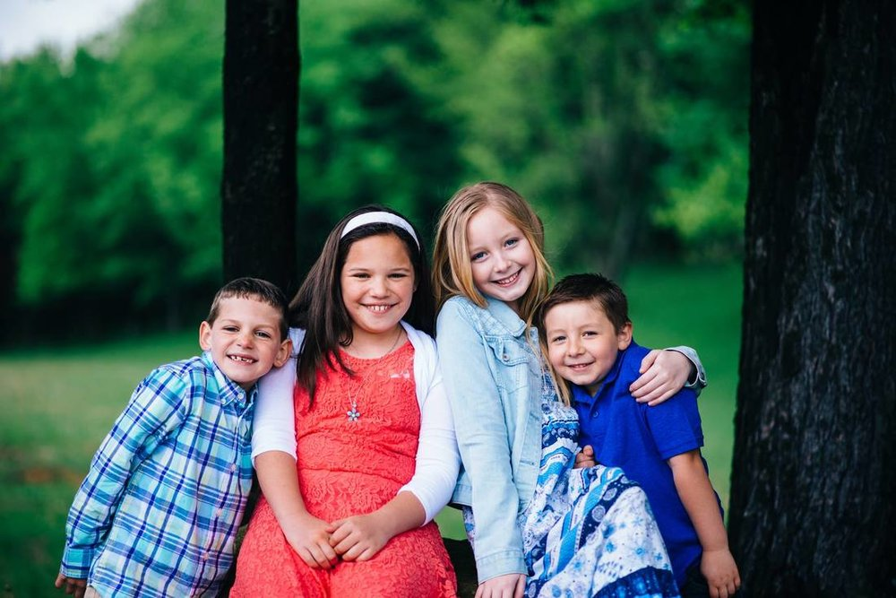 family of four children in close pose as if they are hugging
