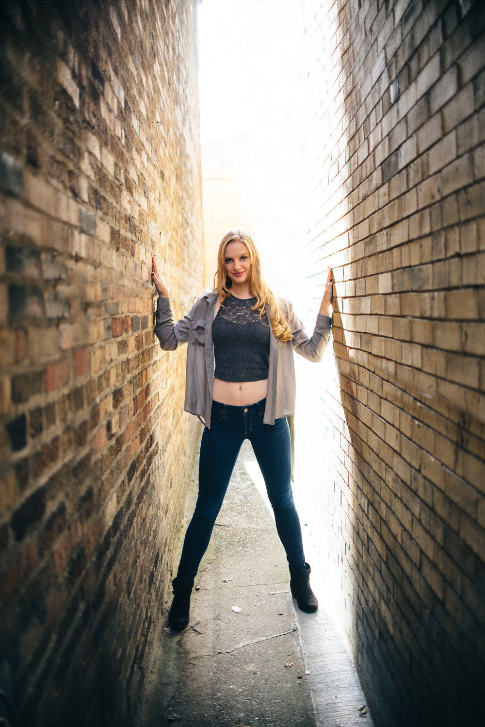 Blonde high school senior model with skinny jeans and gray crop top in urban setting between two brick buildings
