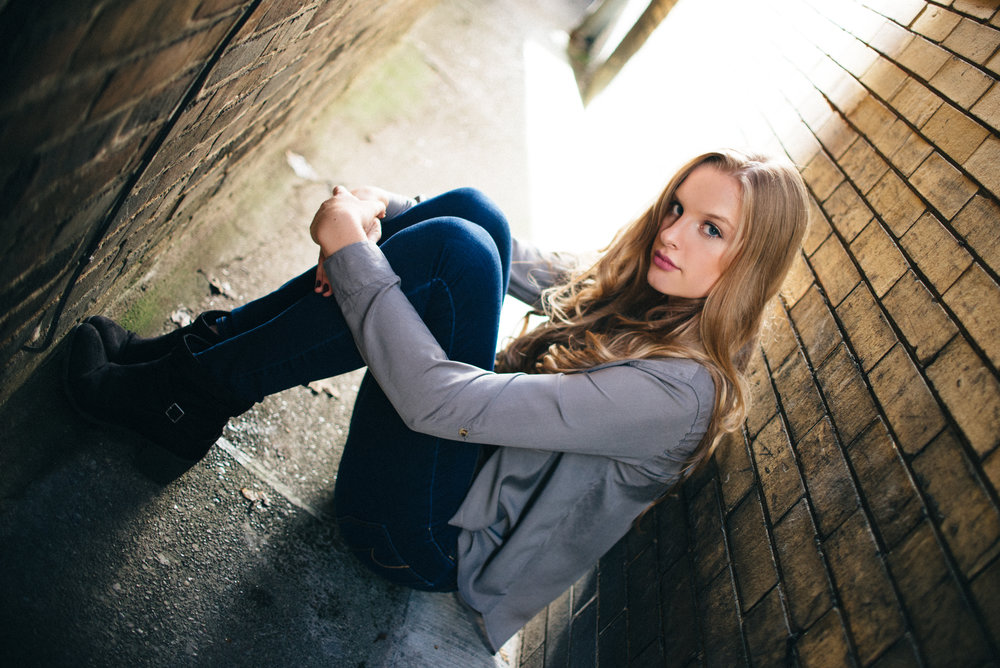 blonde high school model in grey crop top and skinny jeans in a seated pose between two brick buildings in an urban environment