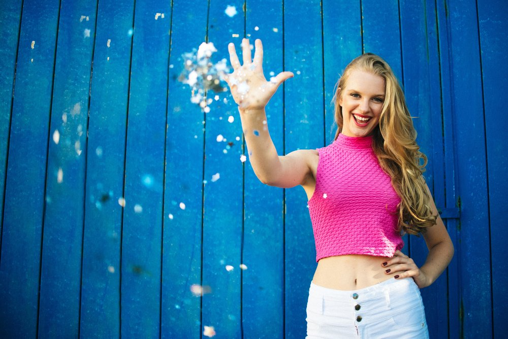 blonde high school senior model in white shorts and hot pink crop top throwing glitter at camera
