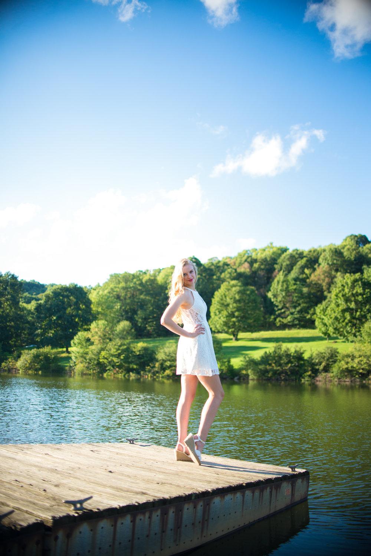 blonde high school senior model standing on lake dock wearing white lace summer dress