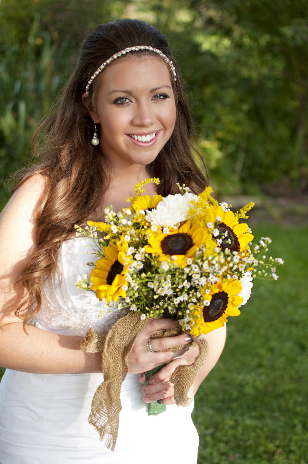 bride with half up hairdo and beaded headband holding sunflower wedding bouquet
