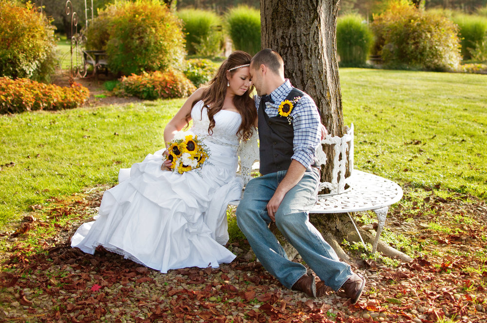 Bride and groom seated on bench touching foreheads
