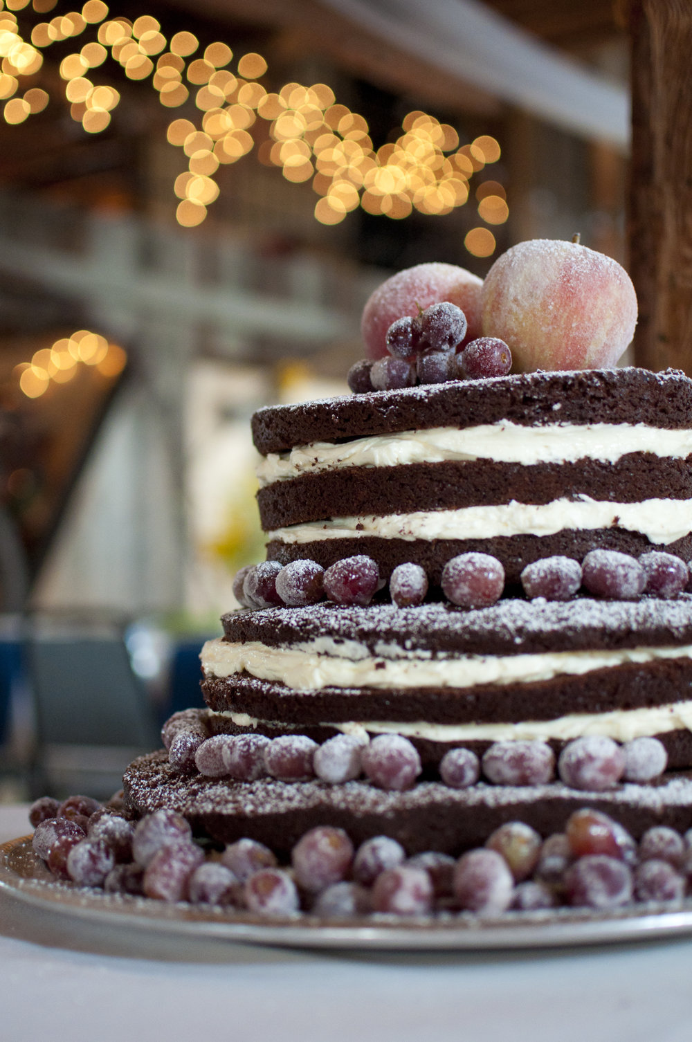 Naked cake with whipped cream filling with sugared fruits on top