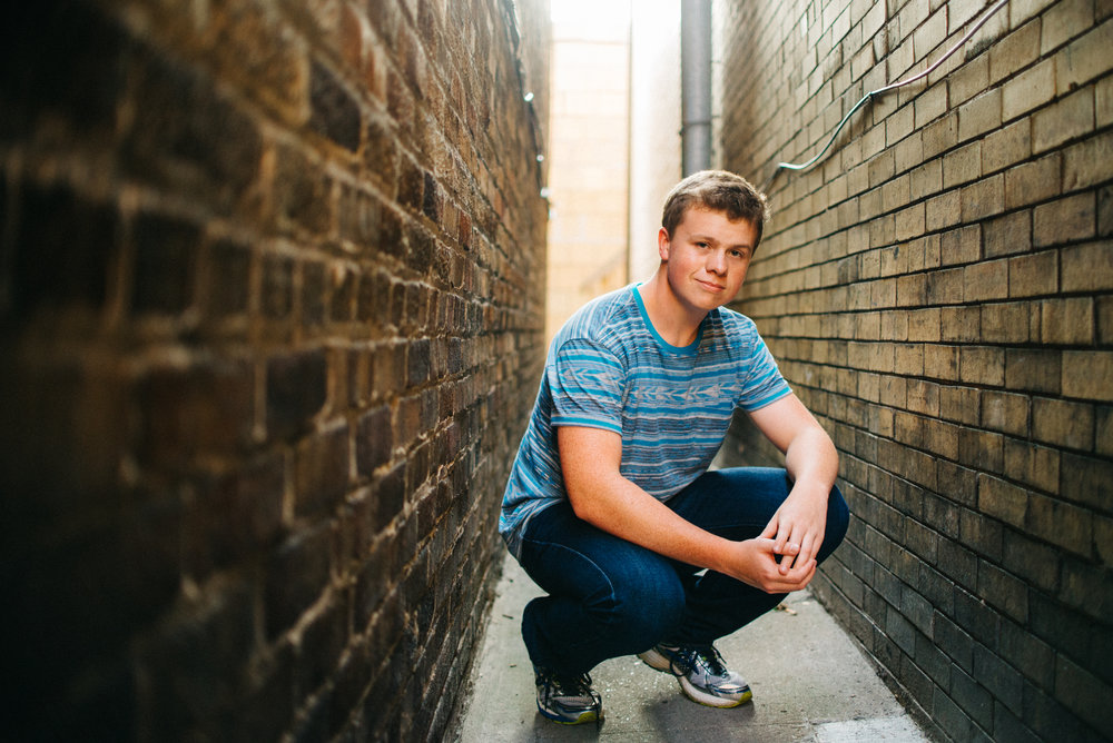 High school senior boy in between brick building in urban setting