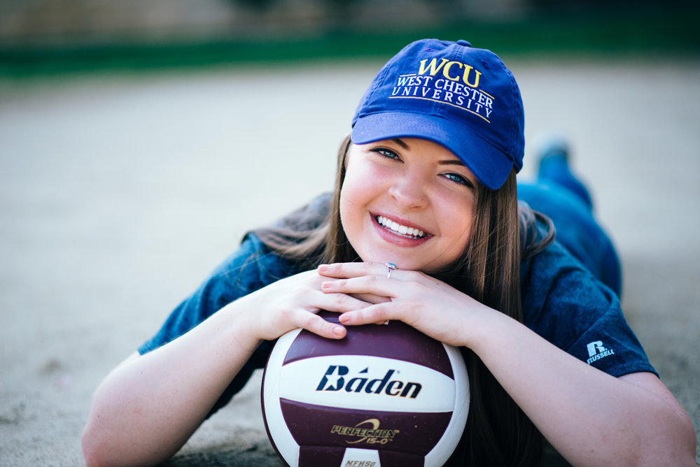 high school senior model posed with purple volleyball wearing a west chester university college hat