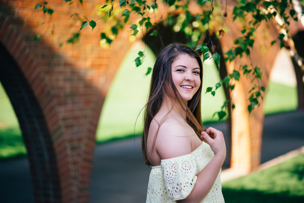 high school senior model with off the shoulder yellow lace top posing in front of arches at the Indiana University of Pennsylvania
