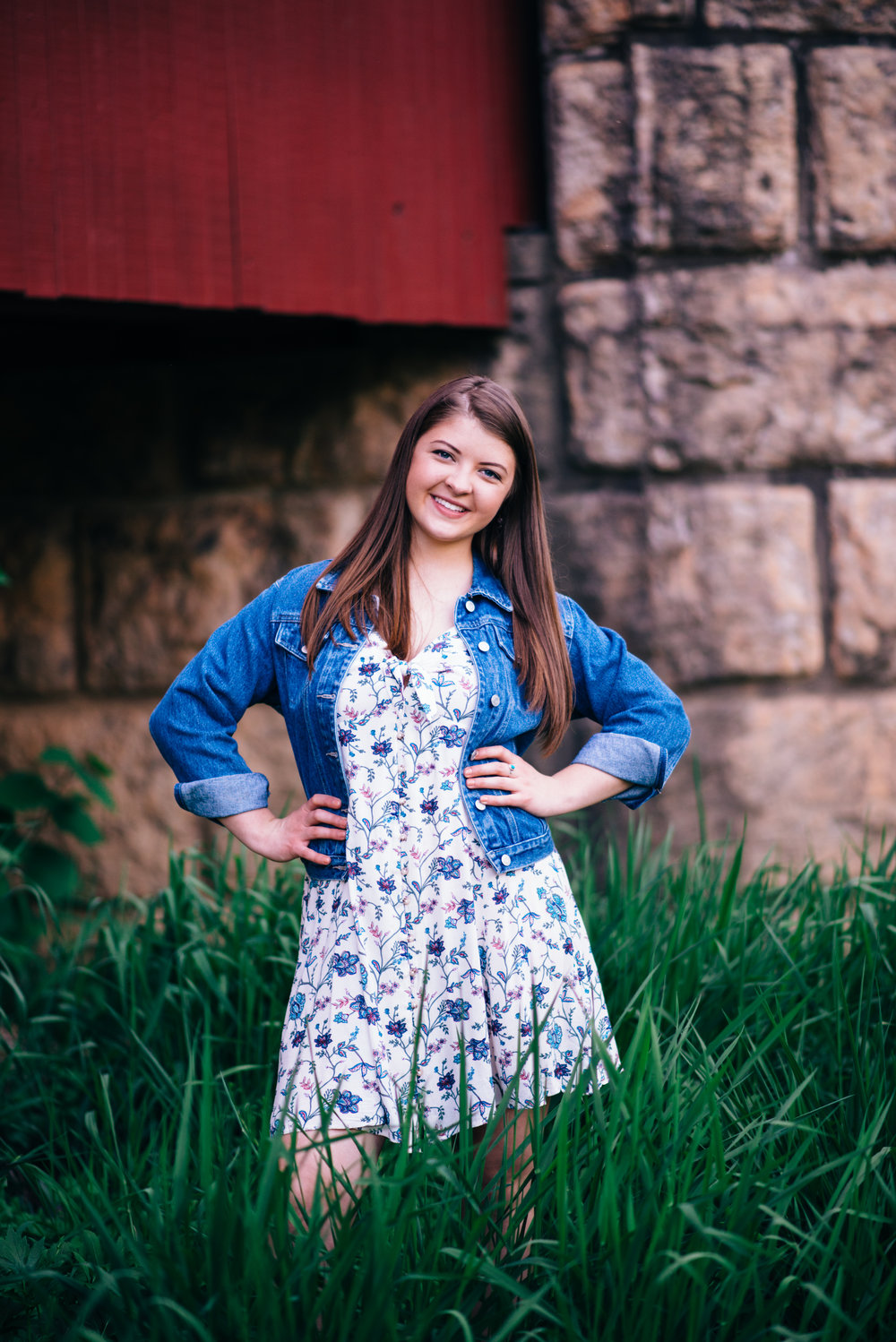 high school senior model standing in front of covered bridge wearing a floral summer dress