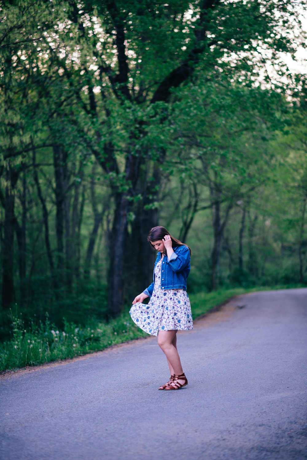 high school senior model twirling floral summer dress on a back country raos with trees