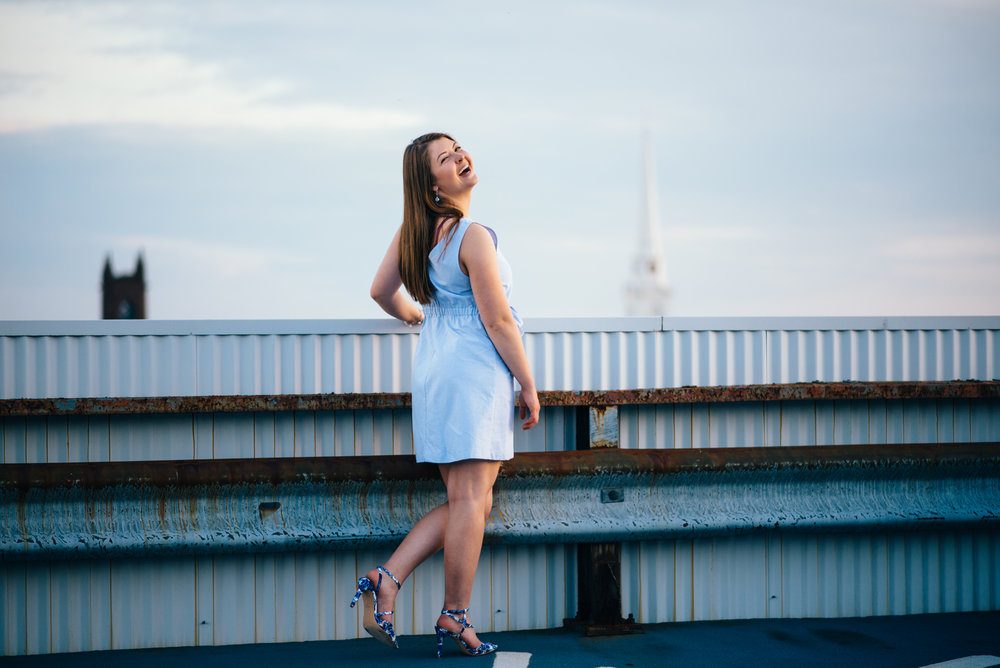 high school senior model wearing light blue shift dress and blue floral heels looking over shoulder and laughing on top of a parking garage in the city