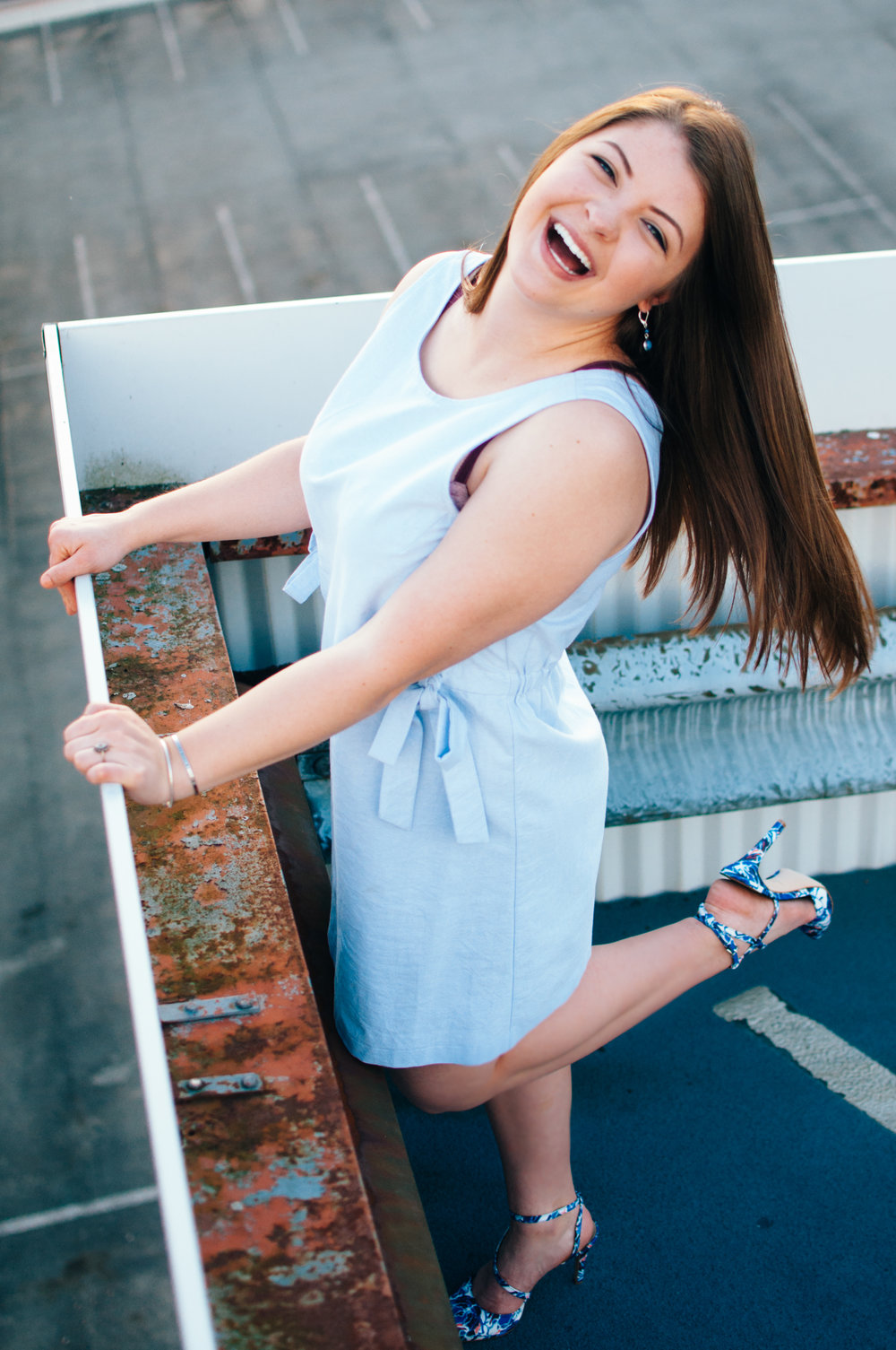 top down shot of high school senior model laughing in light blue shift dress standing on top of parking garage overlooking city of Indiana PA