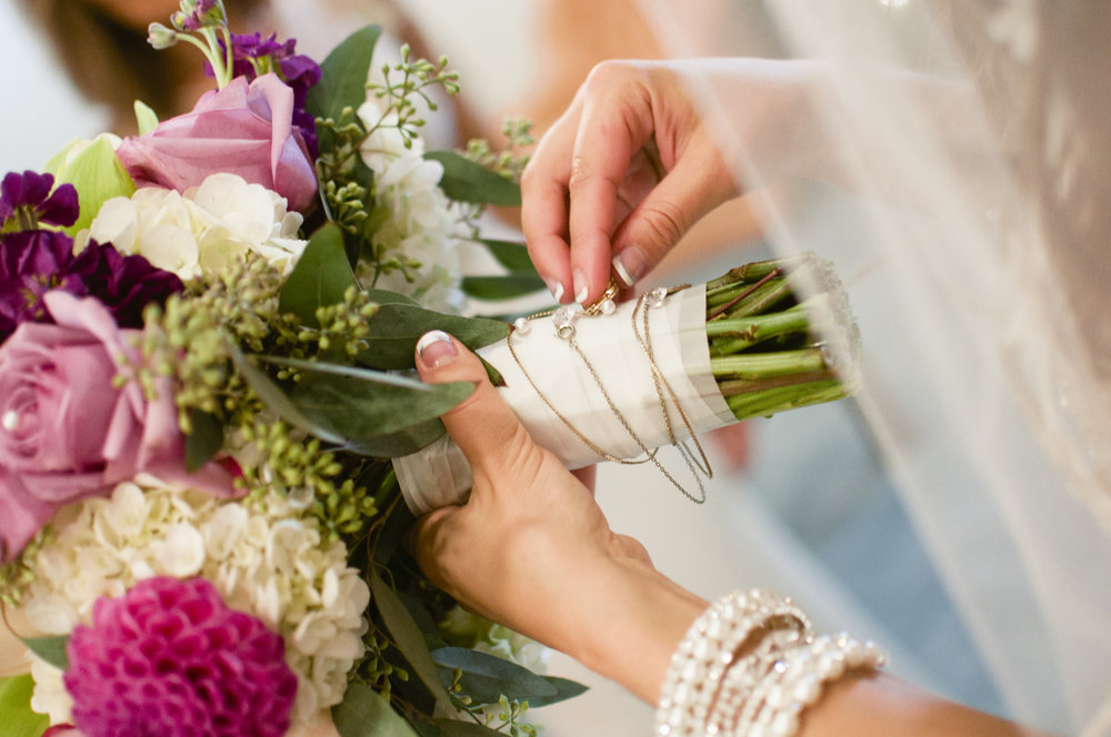 Bride attaching family heirloom to bouquet