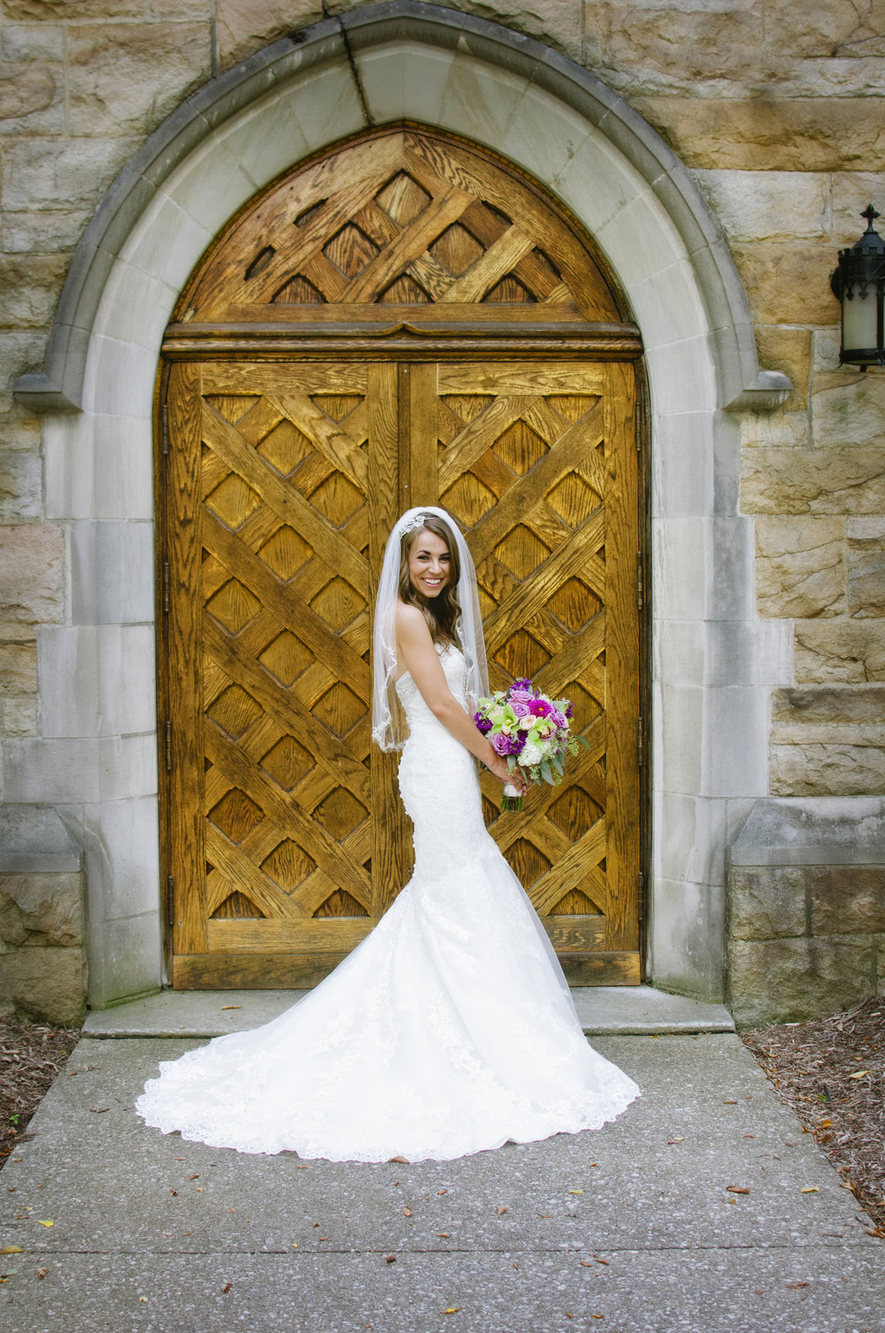 Bride posing in front of large medieval looking wooden door at church