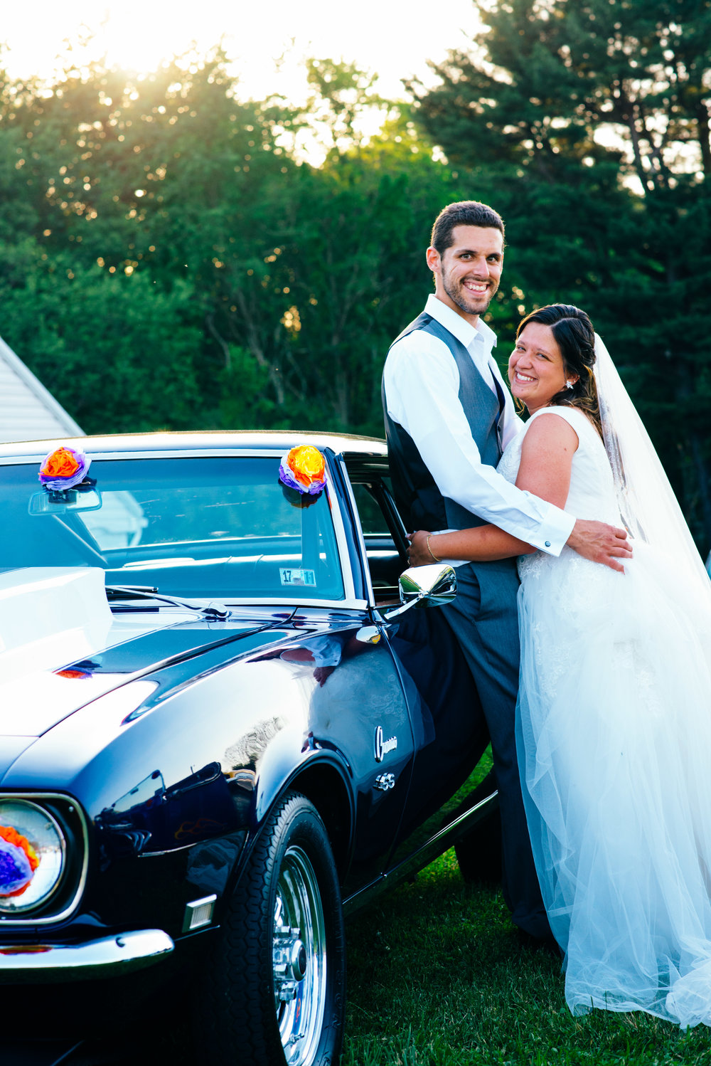 Bride and groom in front of dark blue classic Chevy SS Camaro