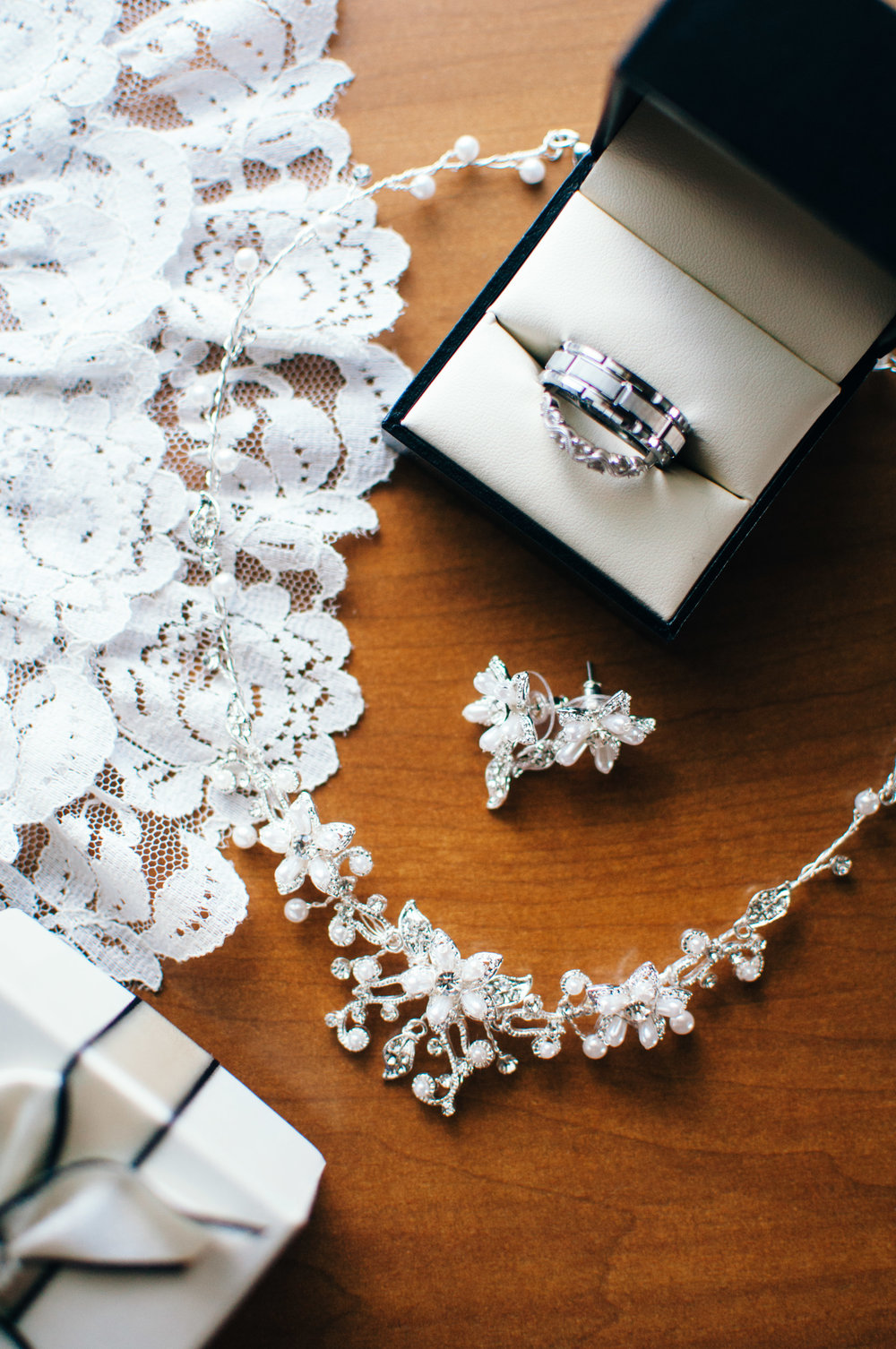 Wedding details like wire necklace with pearls, pearl and silver flower earrings, and family ring heirlooms for luck on the wedding day