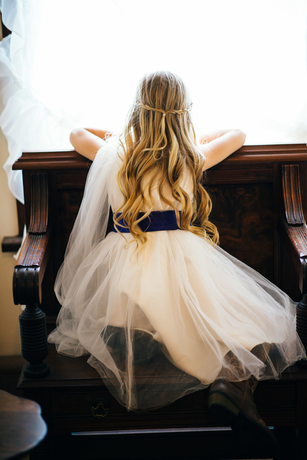 blonde flower girl wearing white dress and cowboy boots looking out of window