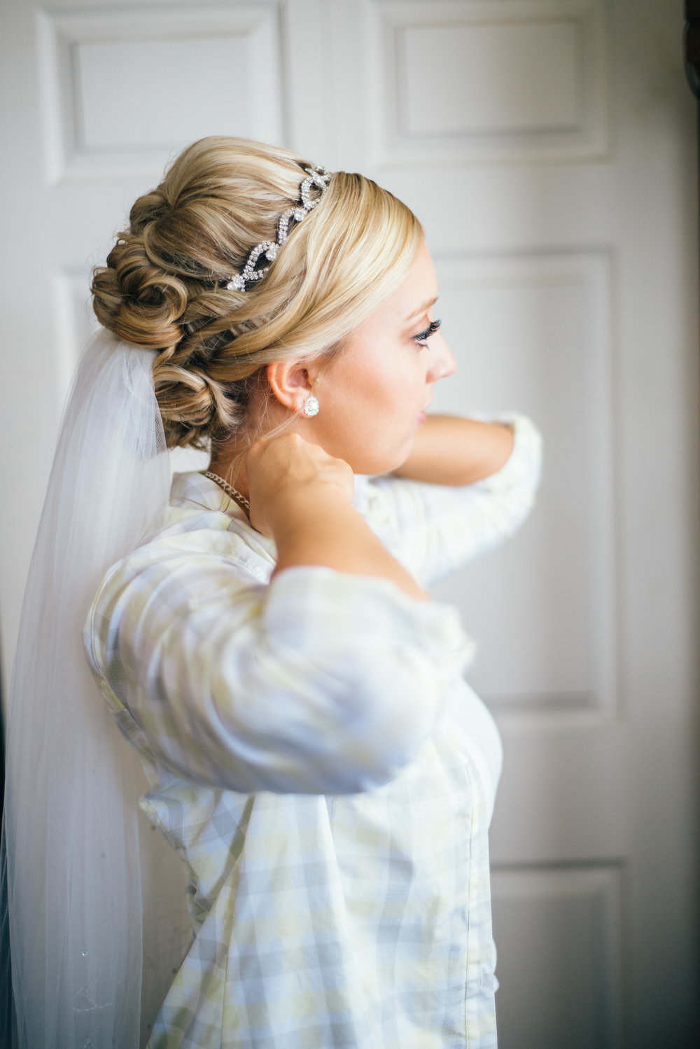 Bride wearing veil clasping necklace before putting on wedding dress